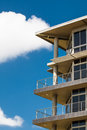 Cropped building an image of a tall storey buildings balconies with a bright blue sky in the background Royalty Free Stock Photo