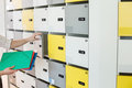 Cropped image of businessman putting files in locker at creative office Royalty Free Stock Photo