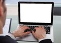 Cropped image of businessman using laptop at desk in office Stock Images