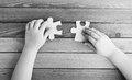 Cropped image of hands connecting two puzzle pieces on wooden table black and white photo Stock Photos