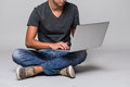 Cropped image of a happy smiling casual man sitting on the floor with laptop Royalty Free Stock Photo