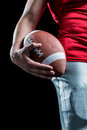 Cropped image of sportsman holding american football against black background Stock Photos