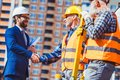 Cropped shot of construction worker in reflective vest shaking hands with businessman Royalty Free Stock Photo