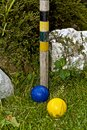 Croquet balls and stake blue yellow alongside a on a green lawn Royalty Free Stock Photos