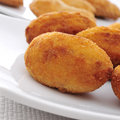 Croquetas spanish croquettes closeup of a plate with on a set table Royalty Free Stock Images