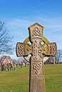 A cross in ancient graveyard an with tombstones the background Royalty Free Stock Image