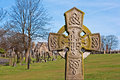 A cross in ancient graveyard an with tombstones the background Stock Images