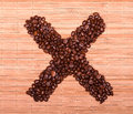 Cross of coffee beans on a decorative straw Royalty Free Stock Photography