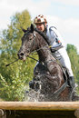 Cross-Country, horseback jumping in splashes water Royalty Free Stock Image