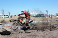 Cross country motor bike race competition in australia with motorbikes racing through mud and water Stock Image
