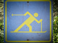 Cross country skiing signboard blue pictorial depicting a very dynamic person on skis x to mark a track against a leafy green Stock Photo