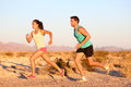 Cross country trail running people at sunset runner couple exercising outside as part of healthy lifestyle multiracial runners Stock Photography
