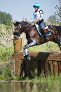 Cross country unidentified rider on horse moscow june is drop fence in water jump obstacle at the international eventing Royalty Free Stock Photos