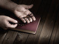 Cross in the hands of wooden christian his palms on bible during prayer Stock Image