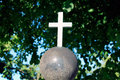 Cross illuminated old stone by sunlight against background of foliage and blue sky Stock Photography