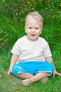 Cross legged little boy sitting on the grass Stock Photo
