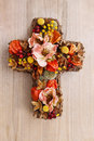 Cross made of artificial flowers and autumn plants. Royalty Free Stock Photo