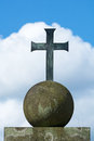 Cross of metal on a stone globe, blue sky with white clouds Royalty Free Stock Photo