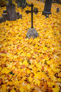 A cross monument in a cemetery with fall leaves the background Royalty Free Stock Photos