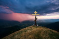 Cross over the valley on a background of dramatic sky with rain Royalty Free Stock Photo