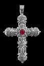Cross pendant with diamonds and rubies in white gold on a black background Stock Photos