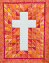 Cross quilt a beautiful red orange and yellow with a white Royalty Free Stock Image