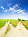 Cross roads horizon with grass and blue sky Stock Photos