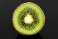 Cross section of kiwi fruit against a black background Stock Photo