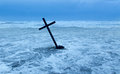 Cross in storm getting pushed over stormy waters Royalty Free Stock Photography