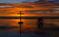 Cross to heal wheel chair by a at a beach as the sunset Royalty Free Stock Photo