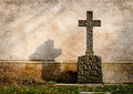 Cross on a tombstone on the background of a dark wall Stock Images