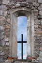 Cross in window of ancient stone church metal with blue sky Stock Images