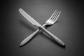 Crossed knife and fork on black background Royalty Free Stock Photos