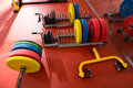 Crossfit fitness gym weight lifting bar equipment colorful on red floor Royalty Free Stock Image