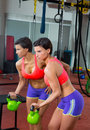 Crossfit fitness lifting kettlebell woman at mirror workout weight exercise gym Stock Photos