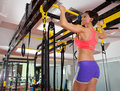 Crossfit fitness toes to bar man pull ups bars with trx woman foot assistant Stock Photo