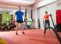 Crossfit gym weight lifting bar man woman battling ropes fitness men and women workout Royalty Free Stock Image