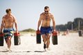 Crossfit men lifting heavy jerrycans strong guys outside on beach muscular active people in s training to maintain healthy Royalty Free Stock Photography