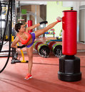 Crossfit woman kick boxing with red punching bag fitness at gym Stock Photography
