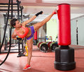 Crossfit woman kick boxing with red punching bag fitness at gym Stock Photo