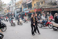 Crossing the streets of hanoi vietnam – february vietnamese women cross street with a slow and steady pace to avoid being hit by Royalty Free Stock Photos