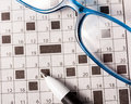 Crossword pen and glasses on the newspaper with Royalty Free Stock Images