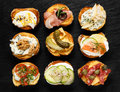 Crostini with different toppings on black background Delicious appetizers Royalty Free Stock Photo
