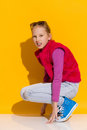 Crouching girl little full length studio shot on yellow background Royalty Free Stock Images