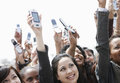 Crowd holding up cellphones multiethnic cell phones against the sky Royalty Free Stock Photos