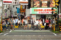 A crowd of Japanese pedestrians wait at a railroad crossing beneath colorful signs. Royalty Free Stock Photo