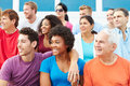 Crowd of spectators watching outdoor sports event smiling Stock Image