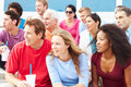 Crowd of spectators watching outdoor sports event smiling off camera Stock Image