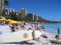 Crowded beach of waikiki honolulu hawaii usa august many people gather on famous is visible in the foreground the surfboard Royalty Free Stock Photos