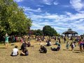 A crowded park of people enjoying the sunshine and the local market